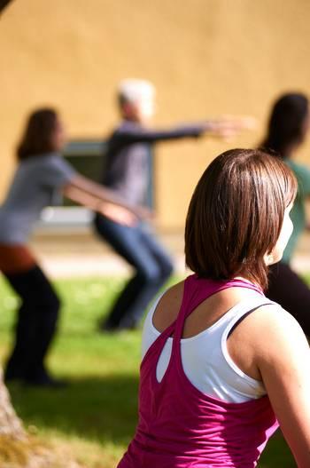 Studentinnen machen Sportübungen auf einer Wiese.