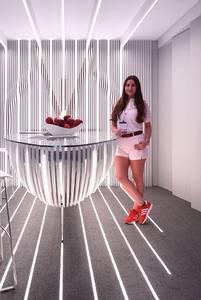 Eine Mitarbeiterin des Messestandes mit roten Schuhen, das Vedder Logo im Hintergrund und rote Äpfel auf der Theke