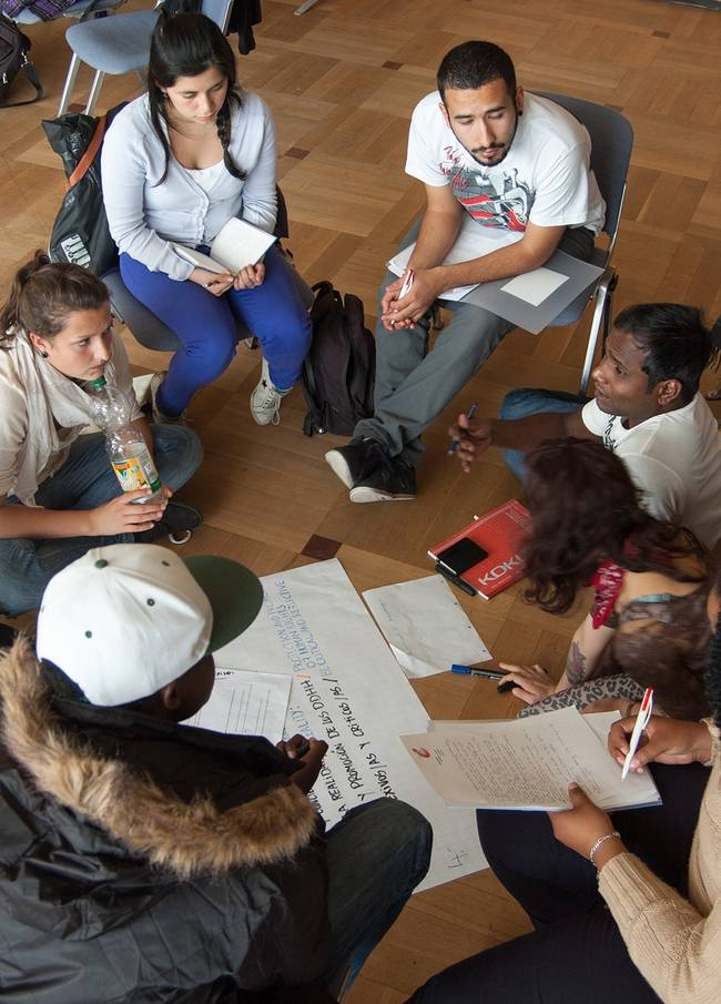 Deutsche und internationale Studierende sitzen im Kreis und sprechen über Soziale Arbeit weltweit.
