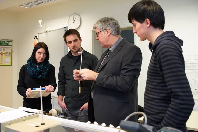 Ein Dozent zeigt drei Studierenden die Möglichkeiten der Gebäudetechnik.
