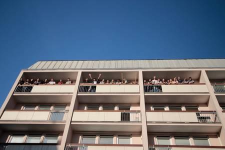 Das Wohnbau-Gebäude von außen. Studierende winken vom Balkon.