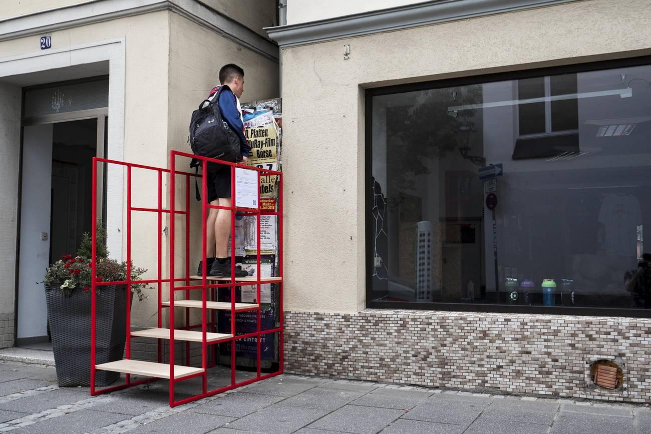Ein Passant steht auf einer Treppe und schaut in den Spalt zwischen zwei Häusern. Bild enthält einen Link.