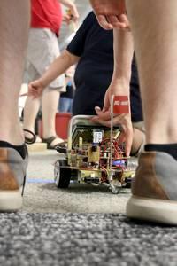 Ein Student setzt den autonom fahrenden Roboter auf die Startlinie.