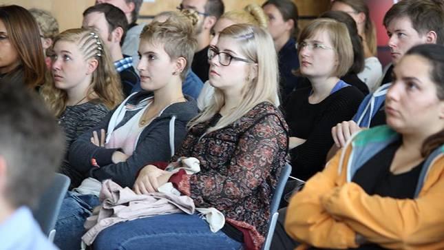 Studierendengruppe aus dem Publikum hört dem Vortrag zu