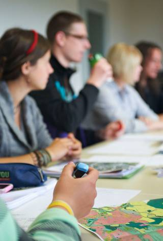 Studierende der Sozialen Arbeit arbeiten an einem Projekt. Der Fokus des Bildes liegt auf der Hand einer Studentin, die einen Stift hält.