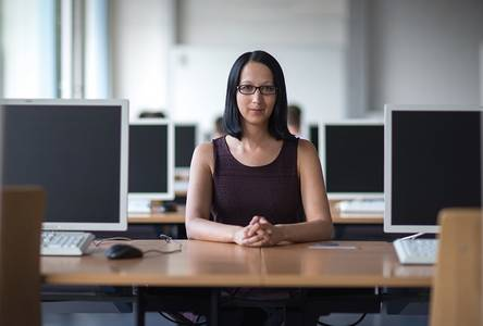 Sarah Wunderlich am Schreibtisch zwischen diversen PC-Bildschirmen