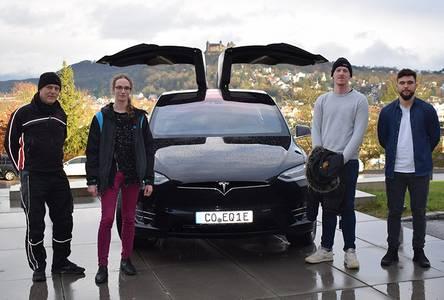 Andreas Stirner mit Georg Braun, Kevin Offermann und Michael Ananin vor dem Tesla mit aufgeklappten Türen auf dem Campusgelände der Hochschule Coburg