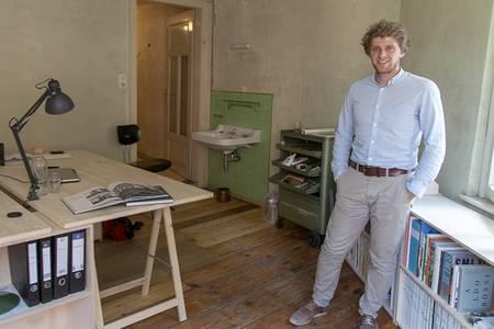 Johannes Wenzel steht in seinem Büro vor einem Holzregal. An der Wand im Hintergrund sind grüne Fließen und ein weißes Waschbecken des Vorbesitzers.