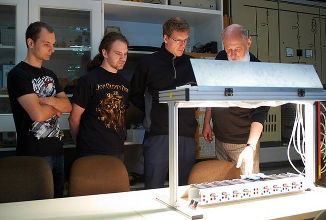 Ein Professor erklärt drei Studenten das Prinzip von Solarzellen.