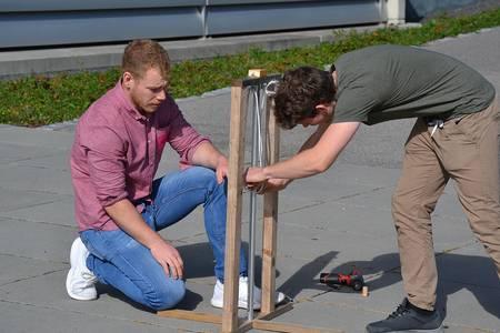 Zwei Studenten bauen ein Katapult.