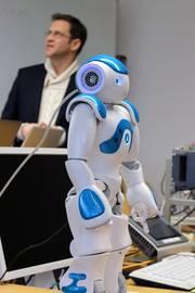 Ein humanoider Roboter - im Hintergrund Prof. Dr. Kolja Kühnlenz
