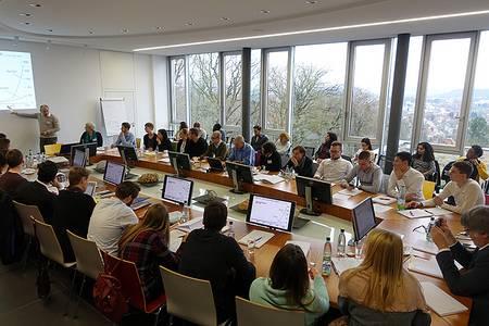 Konferenzteilnehmer sitzen am runden Tisch im Konferenzraum