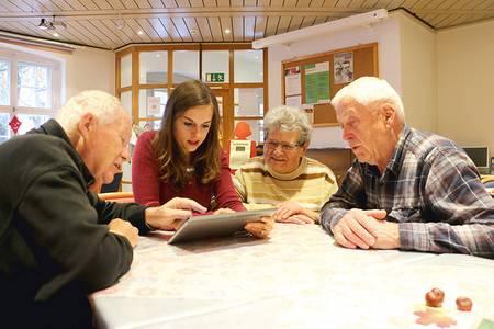 Ältere Menschen und eine junge Frau vor einem Tablet