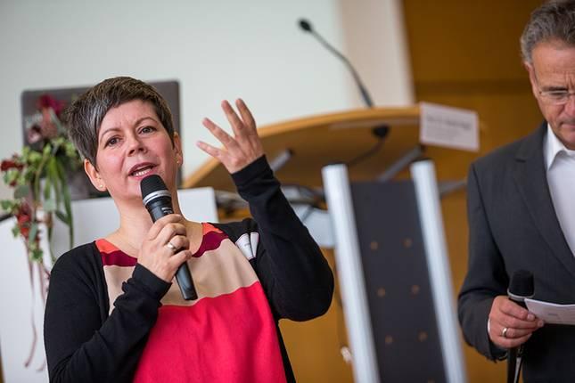 Eine Frau mit Mikrofon redet bei einer Veranstaltung