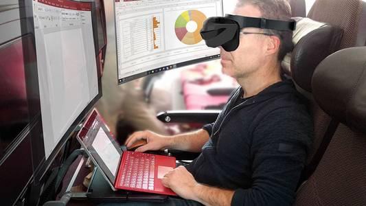 Mensch im Zug mit Laptop und virtuellen Bildschirmen