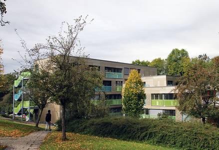 Die Außenfassade des Wohnheims Gotha I hinter Bäumen