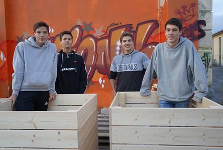 Vier Schüler mit den selbst gebauten Hochbeeten