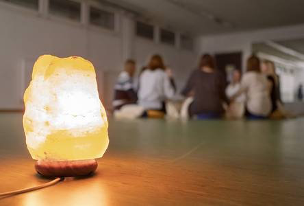 Im Vordergrund eine Salzkristalllampe - im Hintergrund sitzen Studentinnen im Kreis.