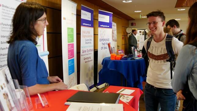 Eine Frau und ein Student unterhalten sich beim Karrieresymposium Bioanalytik.