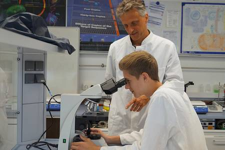 Der Koordinator des TAO-Schülerforschungszentrums, Stefan Gagel, und ein Schüler am Mikroskop