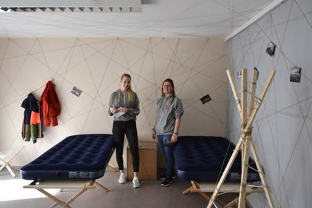 Zwei Studentinnen stehen im Zimmer - neben ihnen zwei Feldbetten auf denen Luftmatratzen liegen