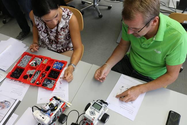 Teilnehmer eines Seminars bauen einen Lego-Fahrroboter.
