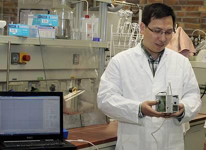 Doktorand Zhu Fan mit einem Sensor