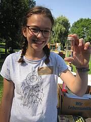 Ein Mädchen hält ein Fläschchen in der Hand.
