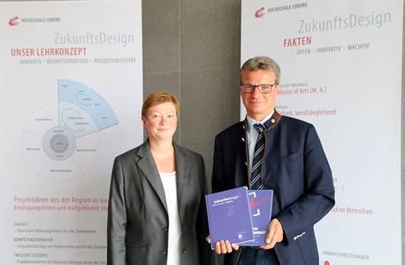 Prof. Dr. Christiane Fritze überreicht Bernd Sibler ein Exemplar des Buchs
