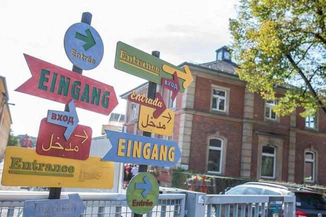 Wegweiser mit der Aufschrift Eingang. Im Hintergrund ein Gebäude - die ehemalige Coburger Schlachthofvilla