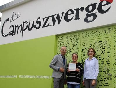 Prof. Dr. Holger Hassel übergibt mit Christina Müller das Zertifikat an Christina Anders