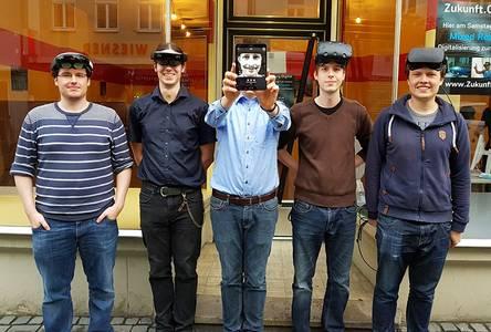 Fünf Studenten stehen nebeneinander, in der Mitte wird ein Smartphone hochgehalten