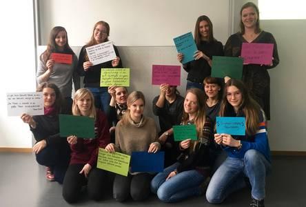 Studentinnen halten bunte Karten hoch, auf die sie Thesen zur Genesungsbegleitung geschrieben haben.
