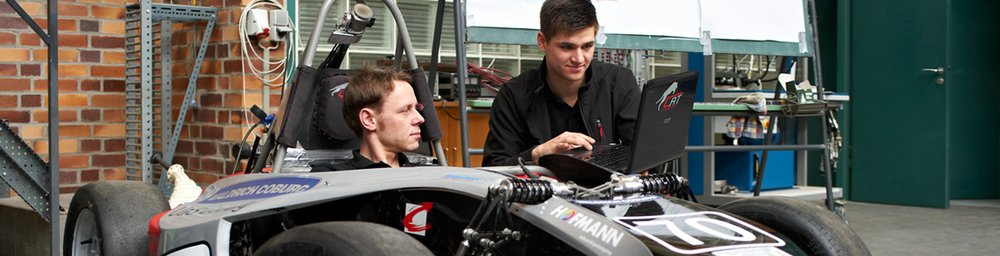 Two men looking at a laptop screen. One kneeling, the other sitting inside a race car.