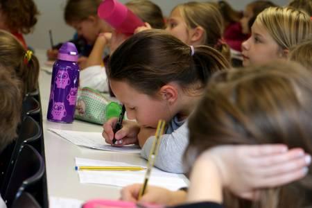 Ein Mädchen schreibt mit einem Stift auf, was sie bei der KinderUni lernt.