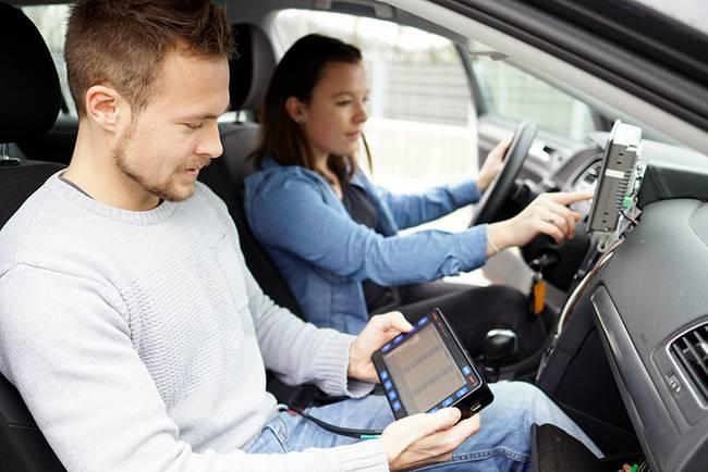 Ein Student und eine Studentin sitzen in einem Auto und testen eine Fahrzeug-Software, die sie selbst entwickelt haben.