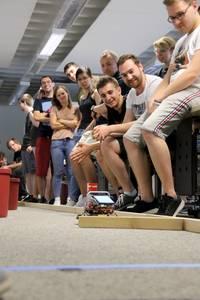 Studierende verfolgen, wie der Roboter versucht, eine Holzleiste zu umfahren.