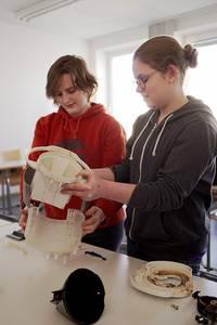 Maren Léa David und eine andere Schülerin bauen eine Kaffeemaschine auseinander