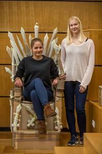 Eine Studentin sitzt auf dem Thron-Stuhl, die andere steht daneben