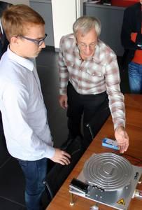 Jonas Göbel und Christian Wolf vor dem Modell des Teilchenbeschleunigers