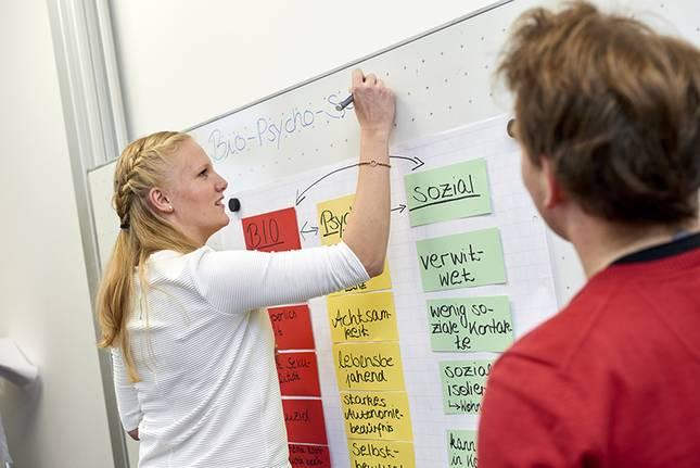 Eine Studentin schreibt auf ein Whiteboard