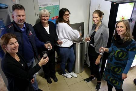 Die sechs Organisatoren stehen mit jeweils einem Glas Wasser um den Trinkbrunnen