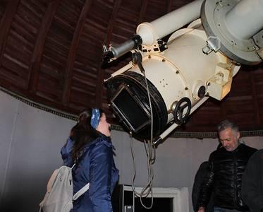 Eine Studentin schaut durch ein Teleskop in den Himmel