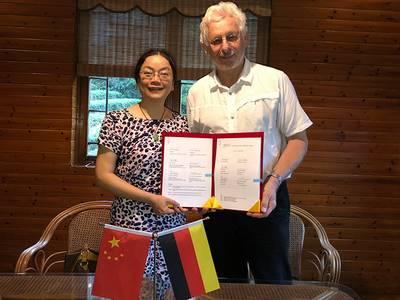 Prof. Dr. Zhu und Prof. Sitzmann halten den Vertrag in den Händen