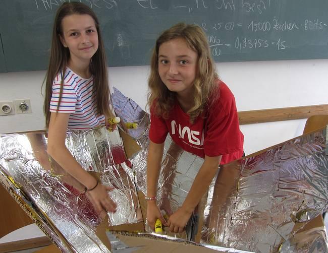Zwei Mädchen bauen mit einem Pappkarton