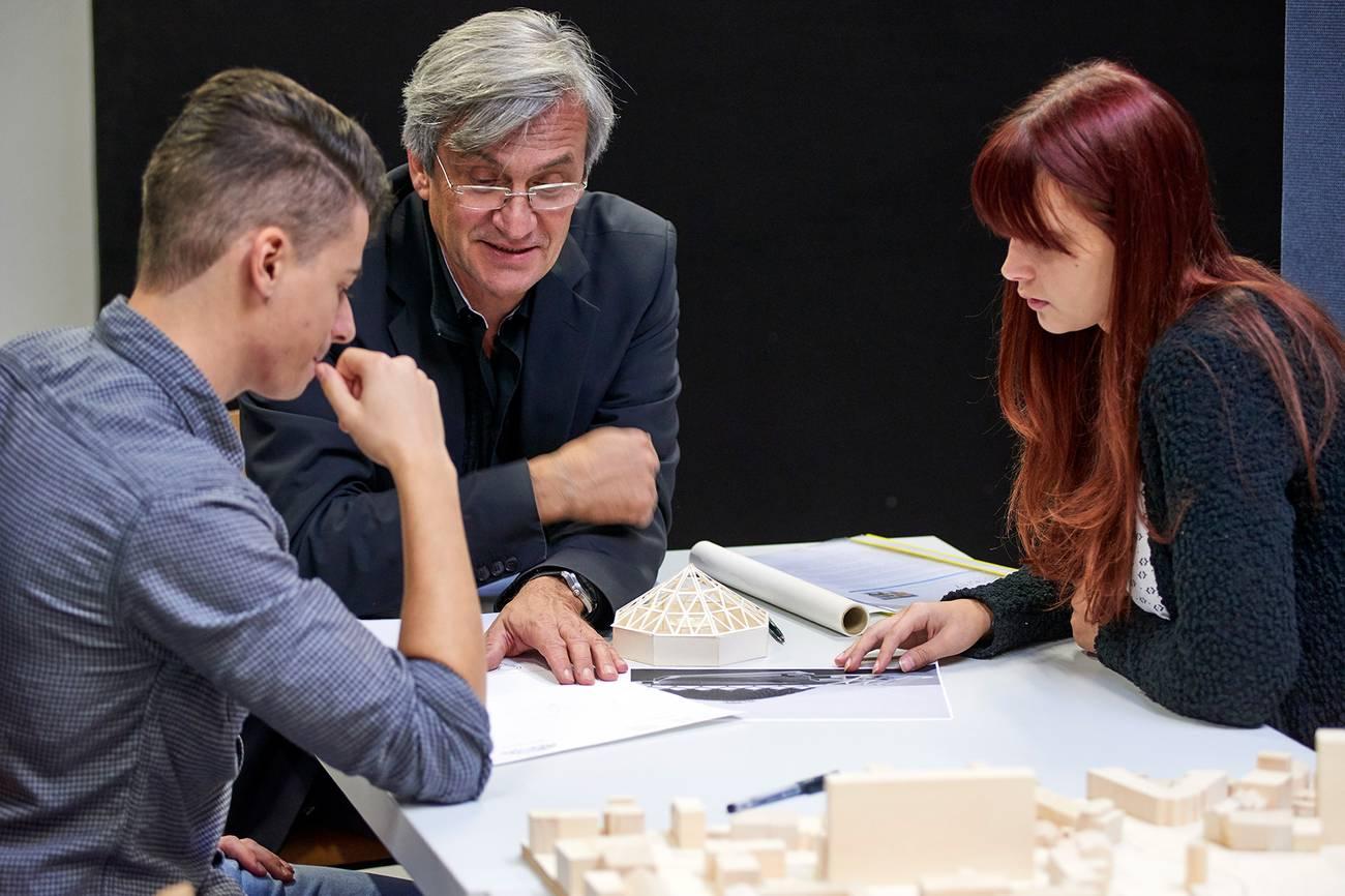 Prof. Dr. Rainer Hirth bespricht mit zwei Studierenden ein Architekturmodell