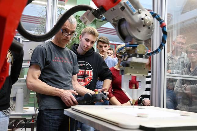 Schüler lernen die Arbeit mit einem Industrieroboter kennen.