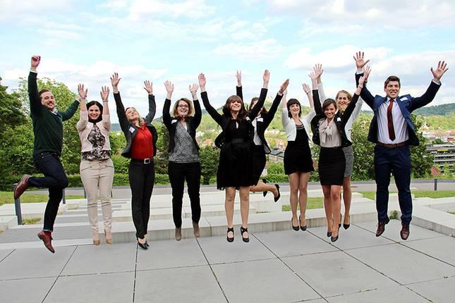 Absolventen des Studiengangs Versicherungswirtschaft springen in die Luft. Im Hintergrund sind die Stadt Coburg und die Veste zu sehen.