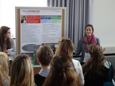 Vortrag neben einem Plakat zur Information