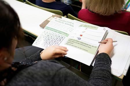 Eine Frau betrachtet eines der Schulhefte, das Studierende der Hochschule entwickelt haben
